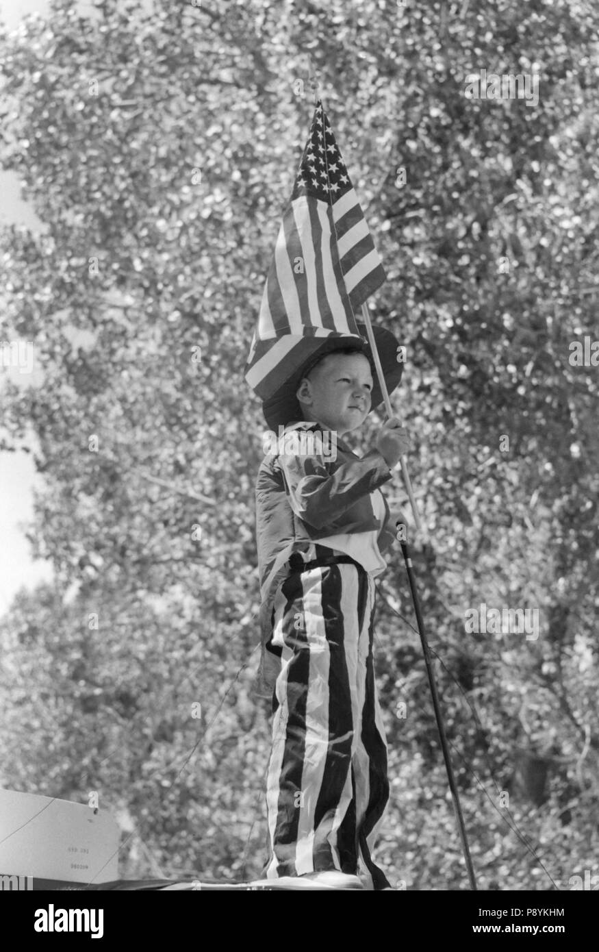 Young Boy in Patriotic Costume Waving American Flag during Fourth of July Parade, Vale, Oregon, USA, Russell Lee, Farm Security Administration, July 1941 - Stock Image