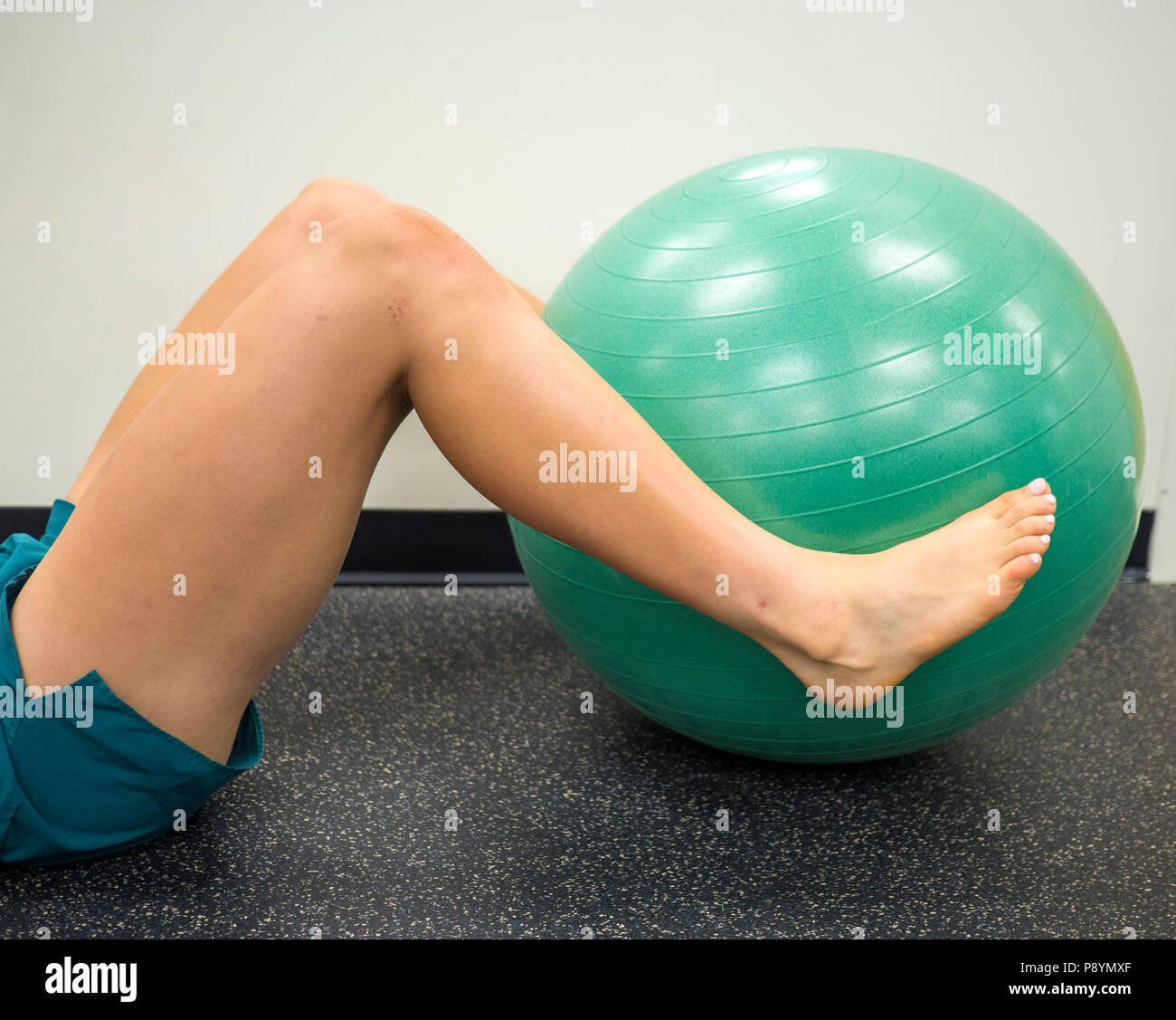 Athlete lying down with her legs around a fitness ball working out and doing exercises - Stock Image