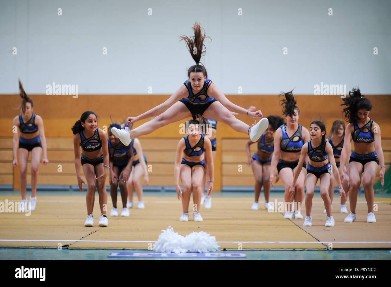 Young teenager cheerleaders dancing, acrobacy, acrobatic moves cheerleaders in blue in the air - Stock Image