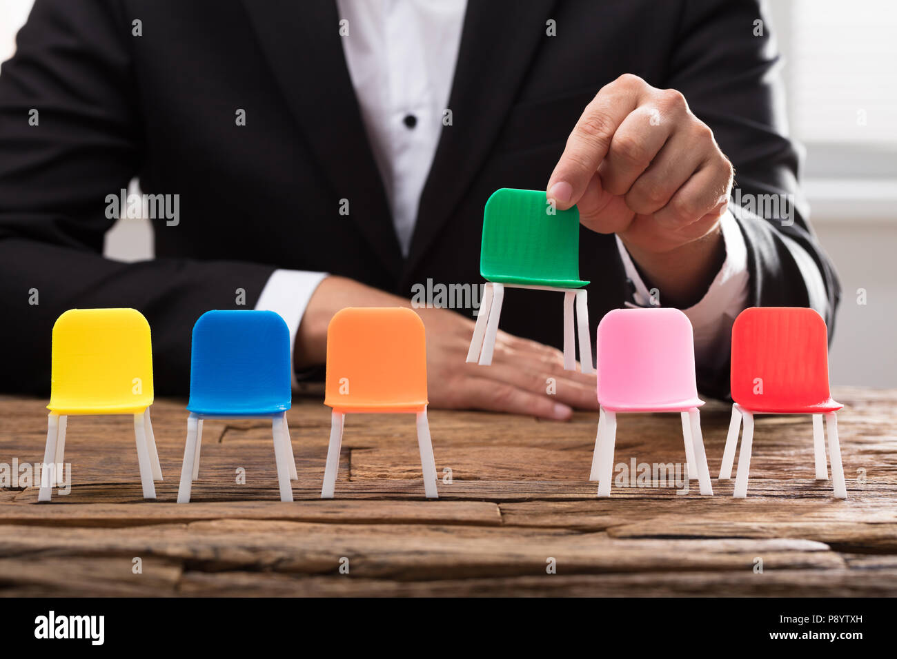 Businessperson's hand picking up green chair among others on wooden desk - Stock Image