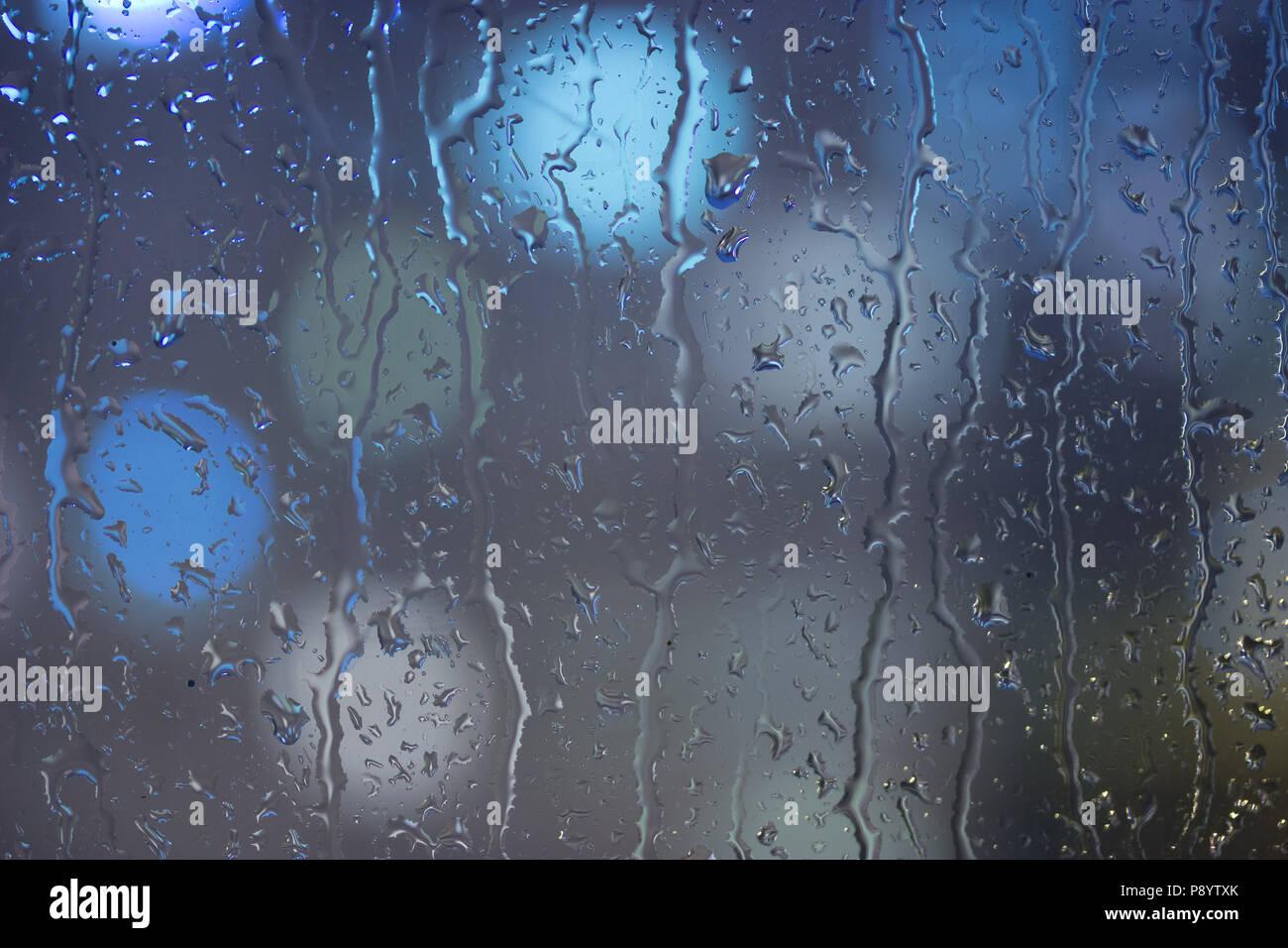 Drops of rain on window, night. blurred light - Stock Image
