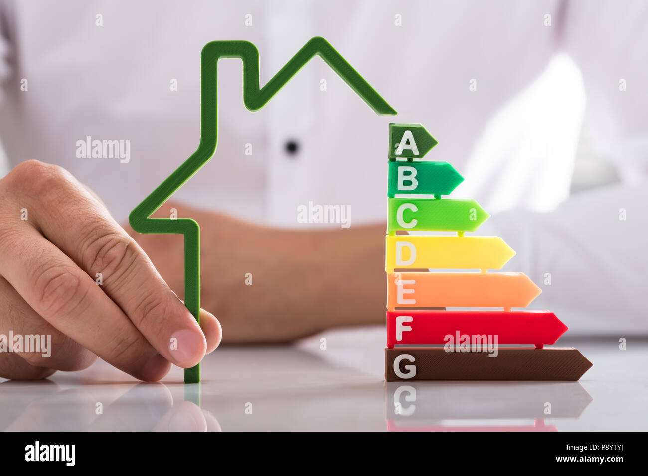 Businessperson's hand holding outline of house model with energy efficiency rate on reflective desk Stock Photo