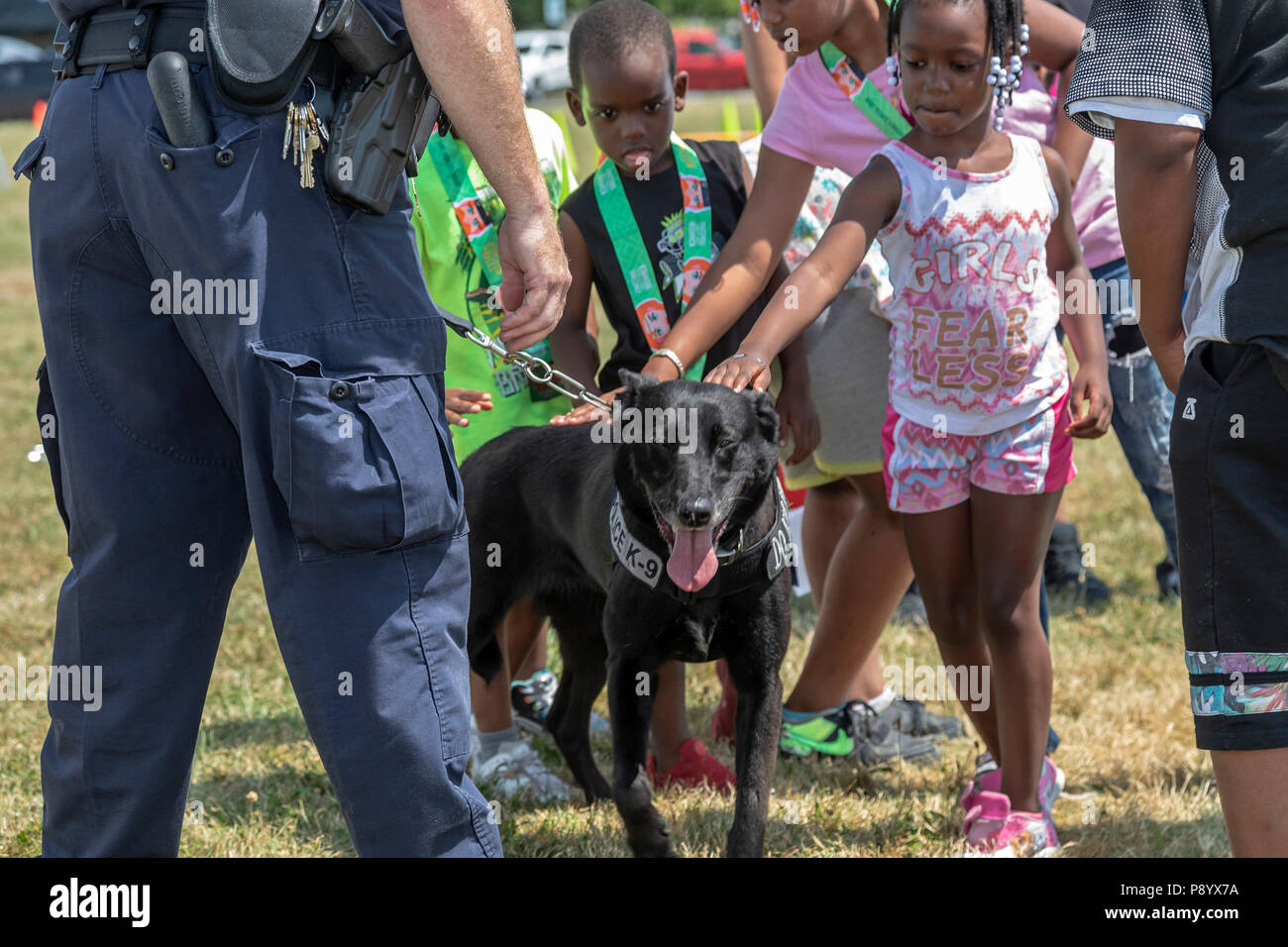 Detroit, Michigan - A U.S. Customs and Border Protection officer shows his dog, Buddy, to children at Metro Detroit Youth Day. Buddy is trained to det - Stock Image