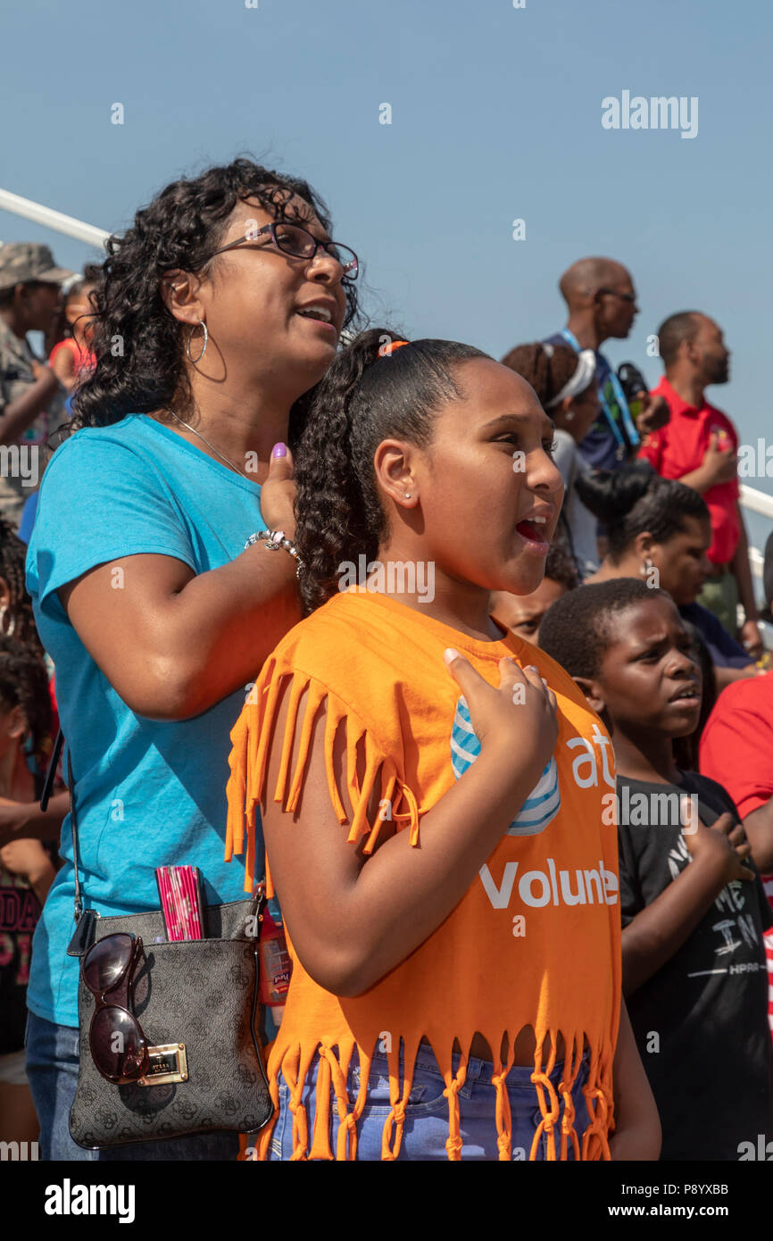Detroit, Michigan - A mother and daughter sing the National Anthem at Metro Detroit Youth Day. Thousands of children aged 8-15 attend the annual event - Stock Image