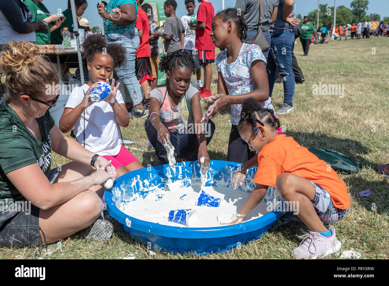 Detroit, Michigan - Children play with oobleck (cornstarch and water) at Michigan State University's booth during Metro Detroit Youth Day. Thousands o - Stock Image