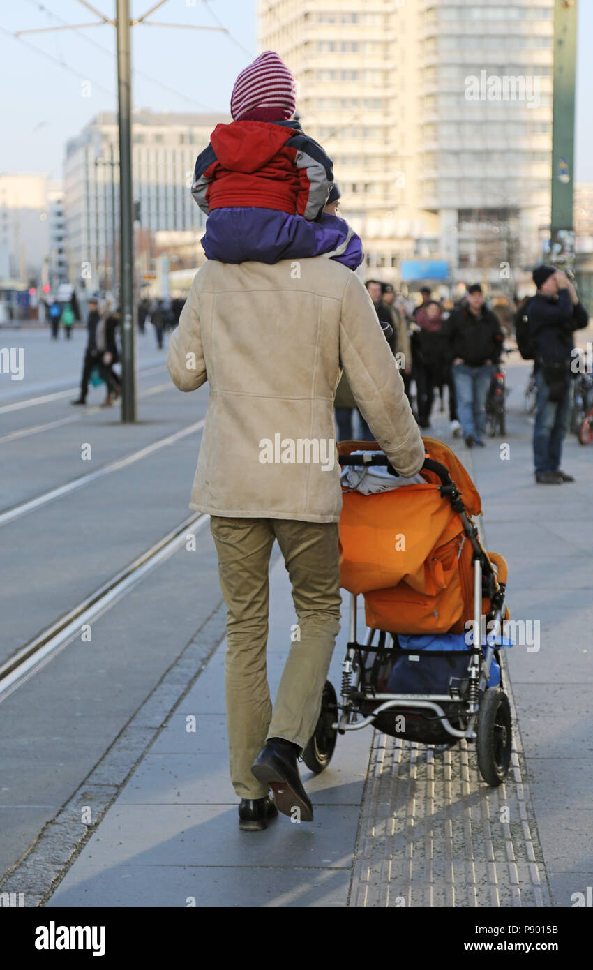 Berlin, Germany, man carries his child on the shoulders and pushes a stroller - Stock Image