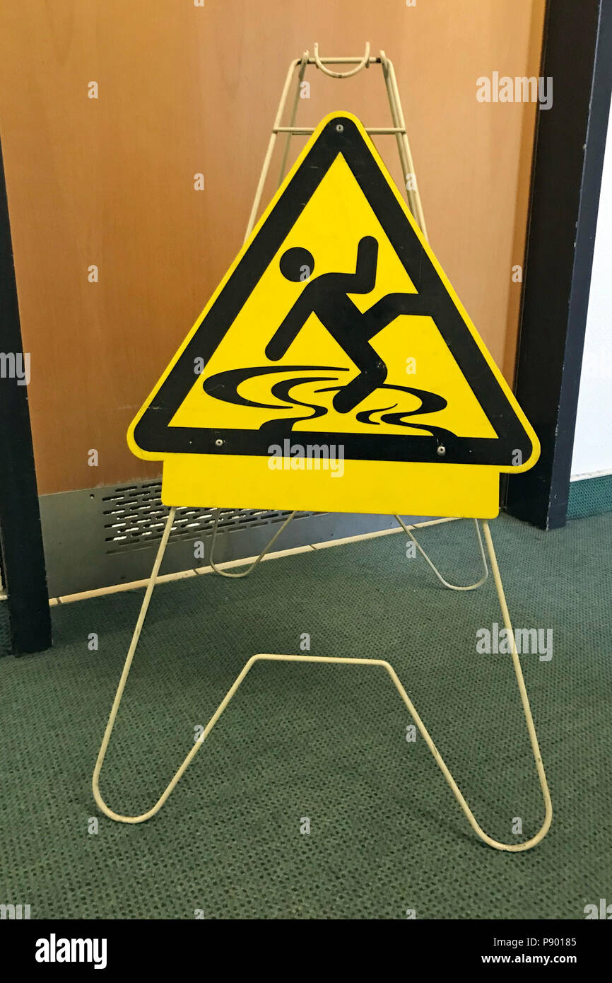 Berlin, Germany, signage danger of slipping in front of a toilet door - Stock Image