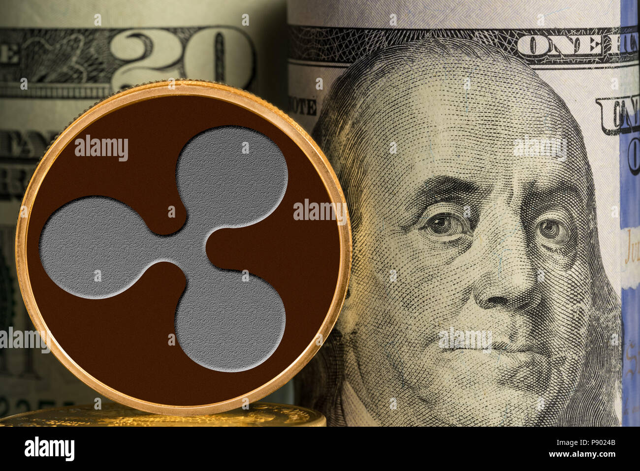 Single Ripple coin in front of bank rolls of US currency - Stock Image