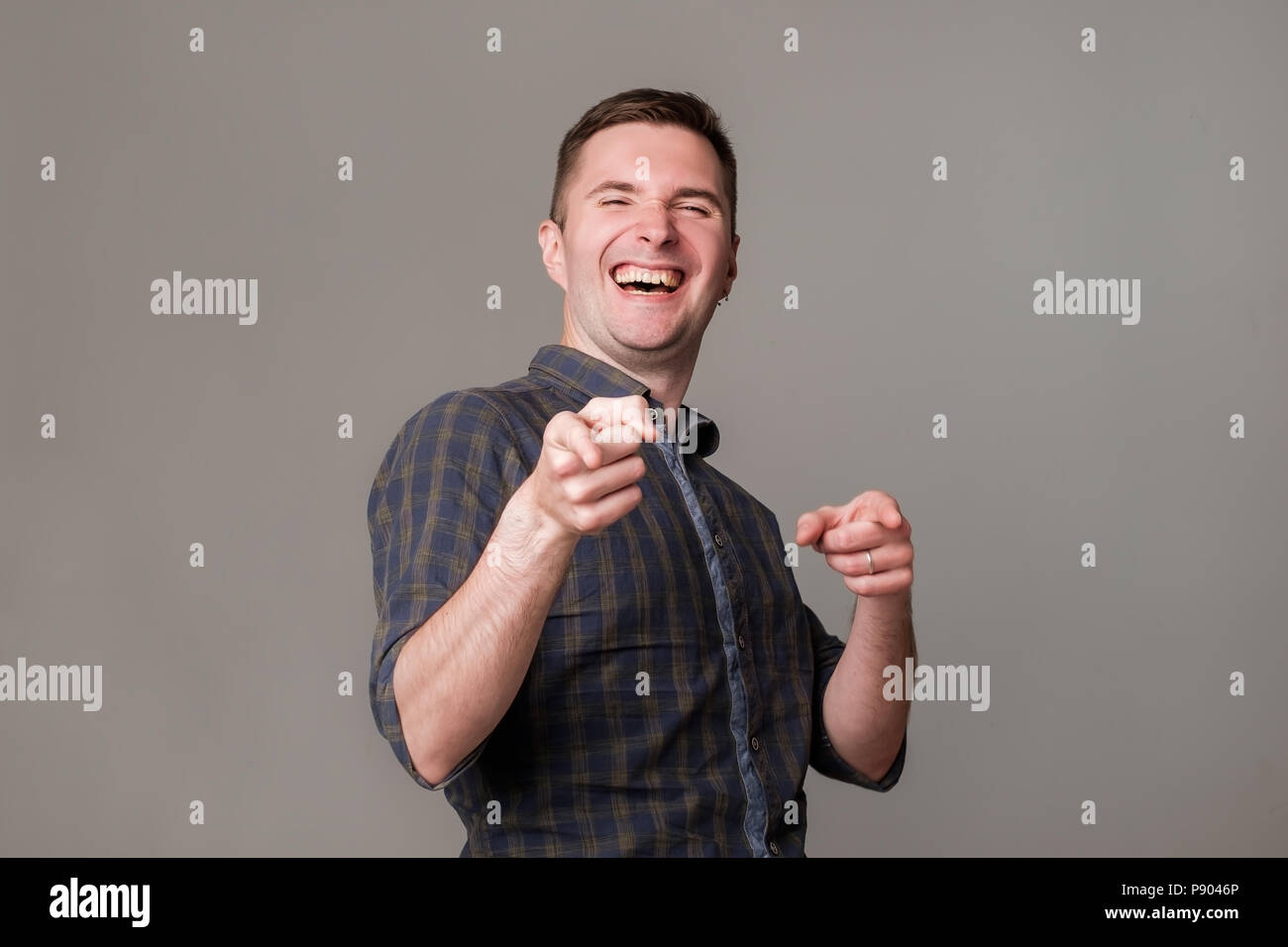 Handsome excited european young man smiling pointing fingers at you. - Stock Image