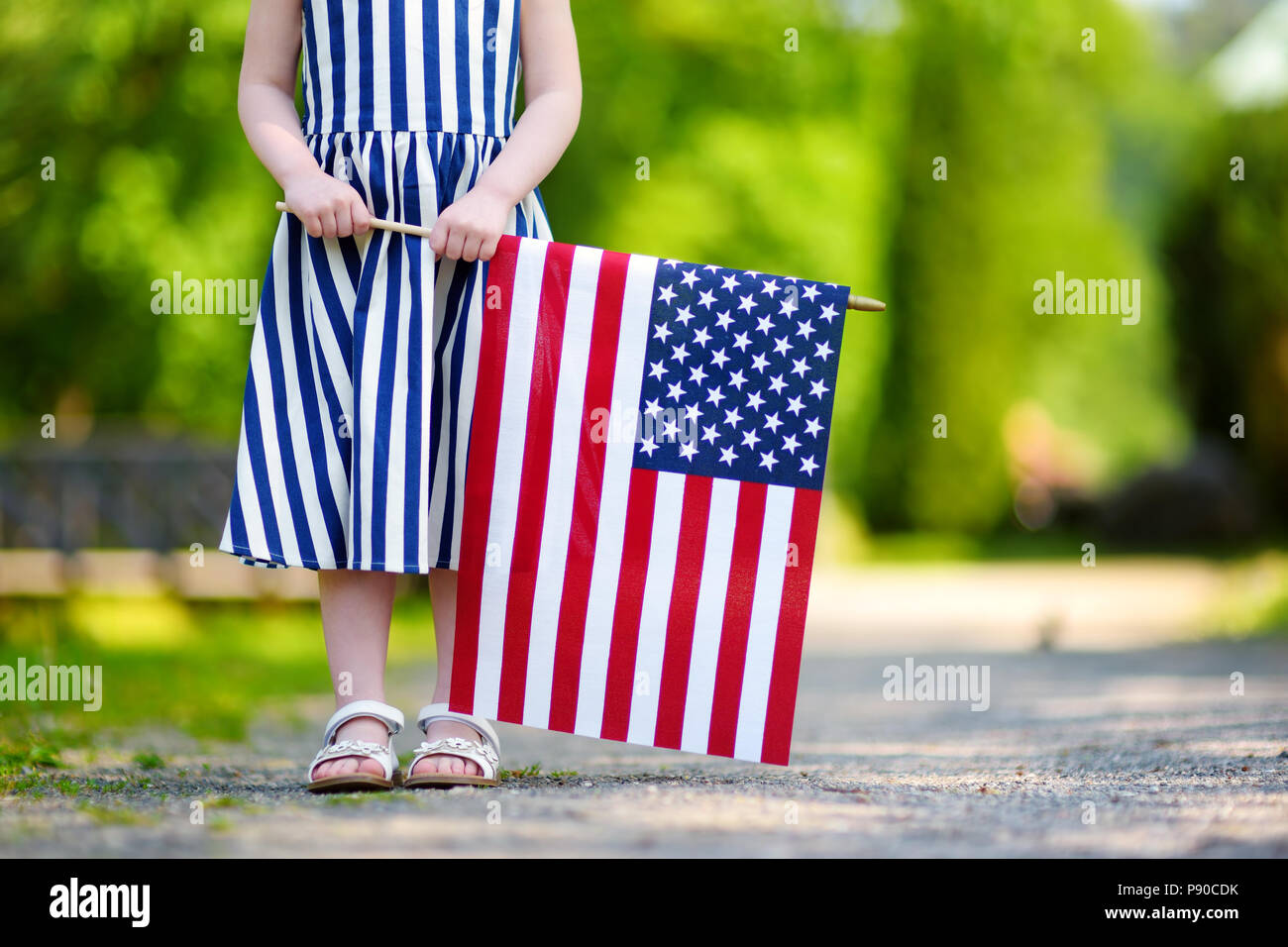 Adorable Little Girl Holding American Flag Outdoors On Beautiful