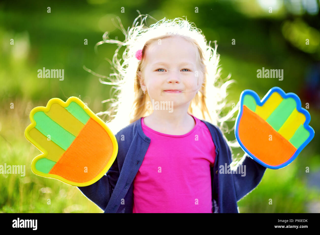 Cute little girl playing a ball catching game with sticky velcro palm pads on beautiful summer day - Stock Image