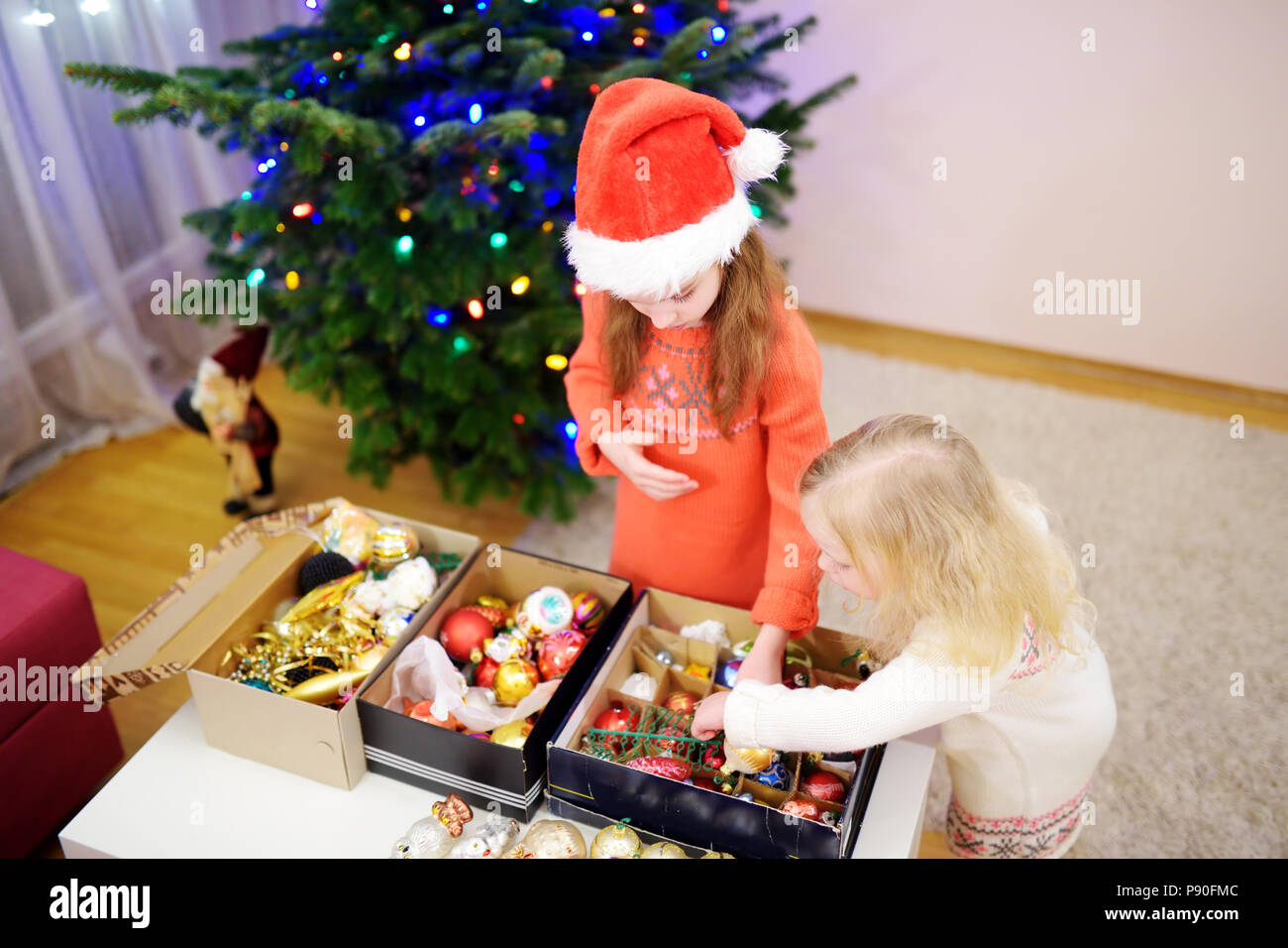 Two Adorable Little Sisters Decorating A Christmas Tree At Home