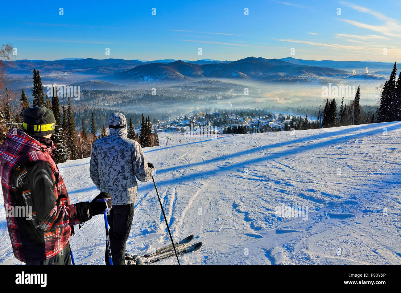 RUSSIA, SIBERIA, SHEREGESH - JANUARY 11, 2016: Two young skiers stands on top of a winter mountain and admire of view frosty mountain scenery and the  - Stock Image