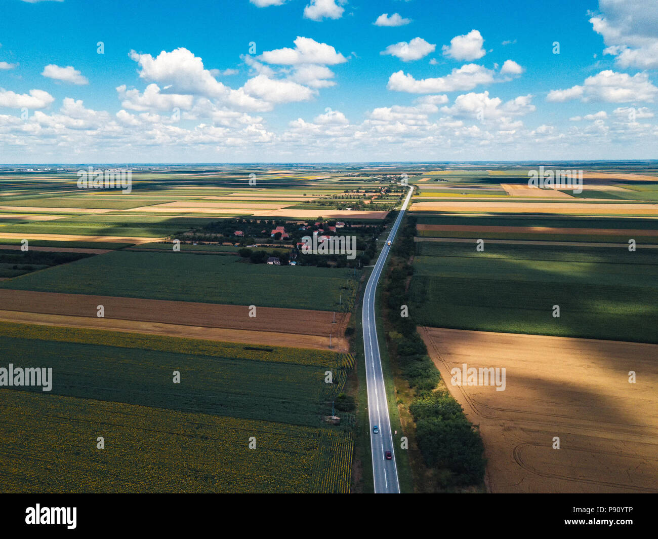 Aerial view of road through countryside landscape on sunny summer day - Stock Image
