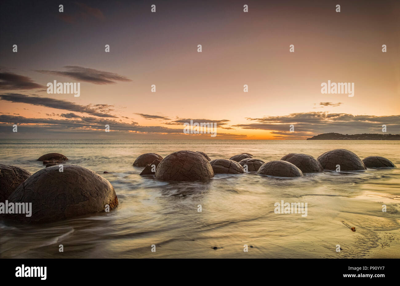The famous Moeraki Boulders, an icon of New Zealand, in Otago, at sunrise. - Stock Image