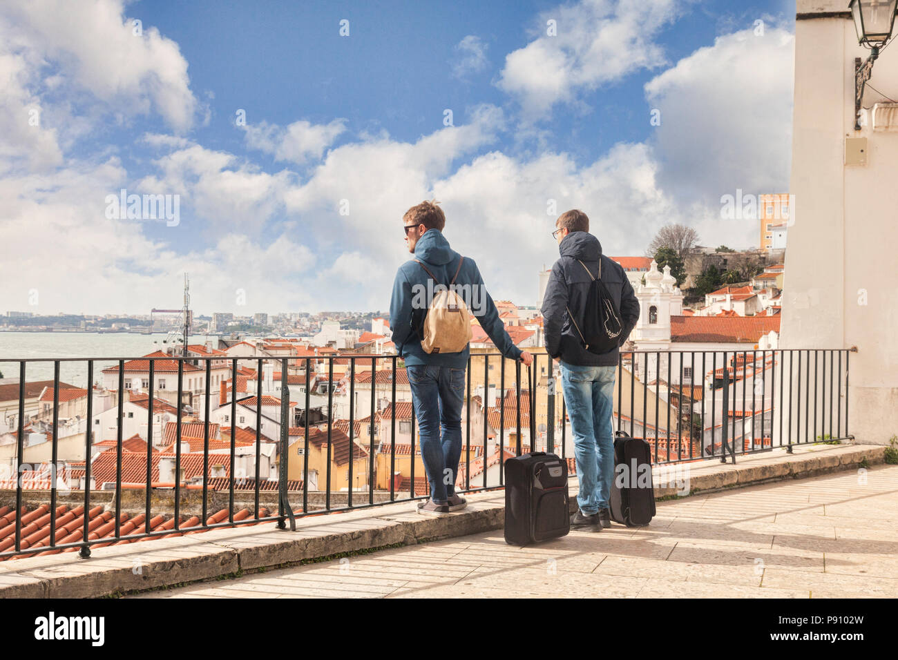 7 March 2018: Lisbon, Portugal - Two young males with carry on luggage looking at the view of the city from Miradouro de Santa Estevao. - Stock Image