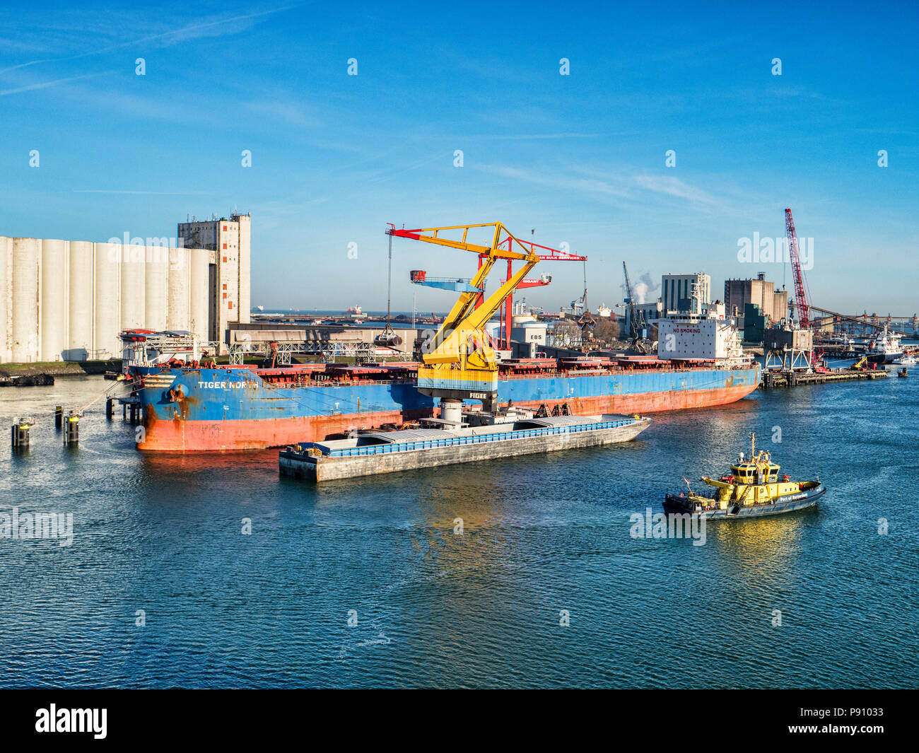 6 April 2018: Rotterdam, Netherlands - Bulk carrier Tiger North  being unloaded at Port of Rotterdam on a bright spring morning with clear blue sky. - Stock Image