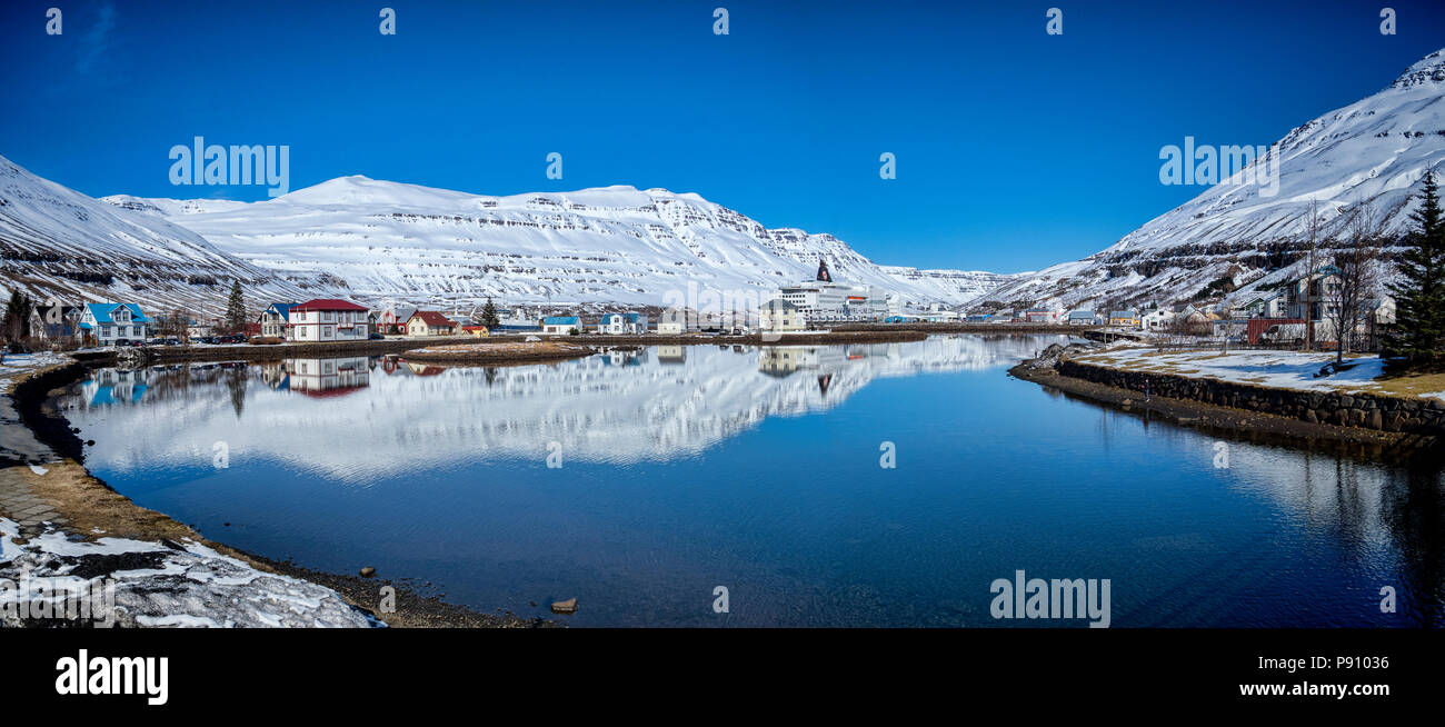 11 April 2018: Iceland - The East Iceland port of Seydisfjordur, with the Smyril Line ship Norrona moored at the quay. - Stock Image