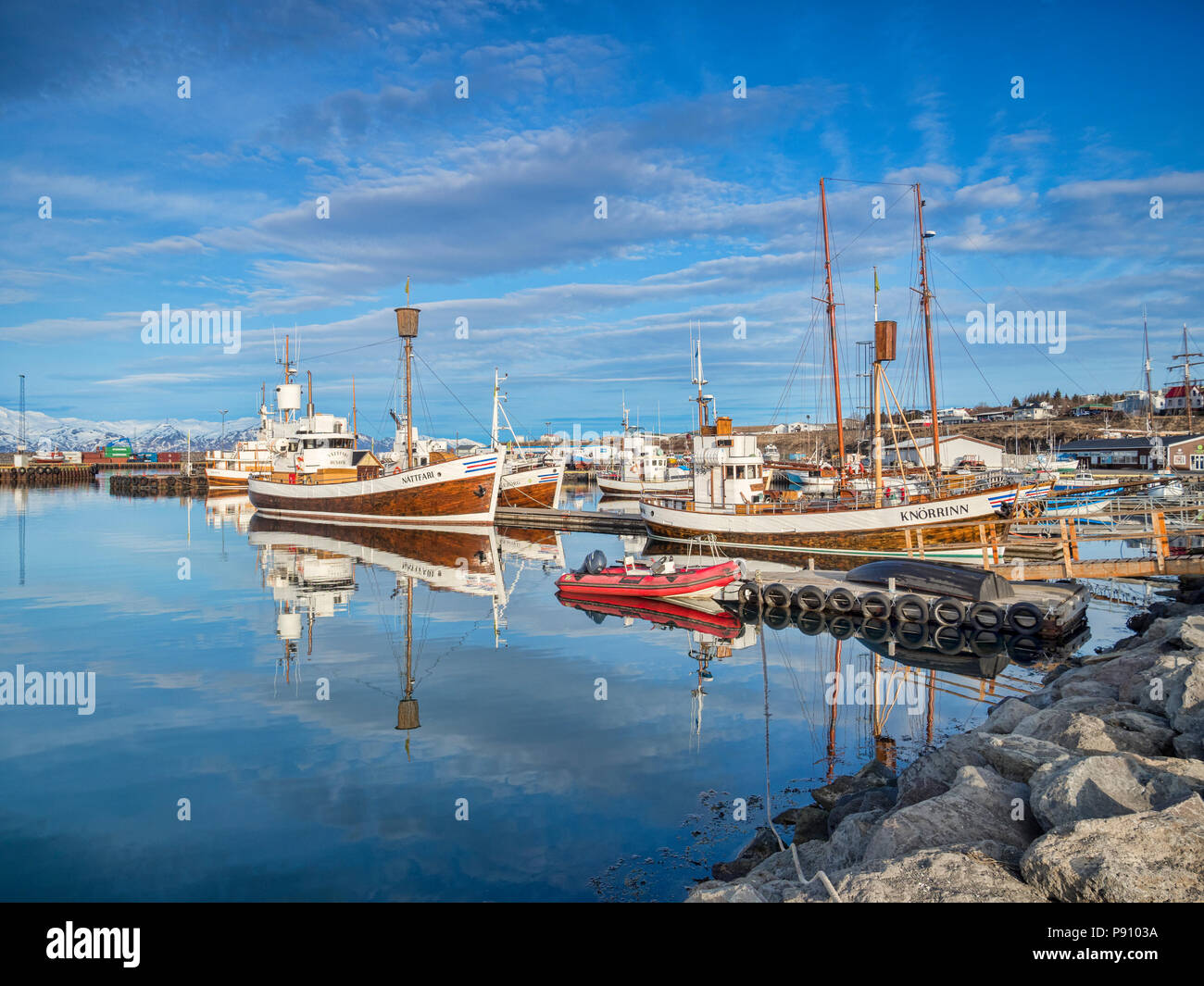 13 April 2018: Husavik, Iceland. The harbour at Husavik in Northern Iceland, with boats, including whale-watching vessels, reflected in the calm water - Stock Image