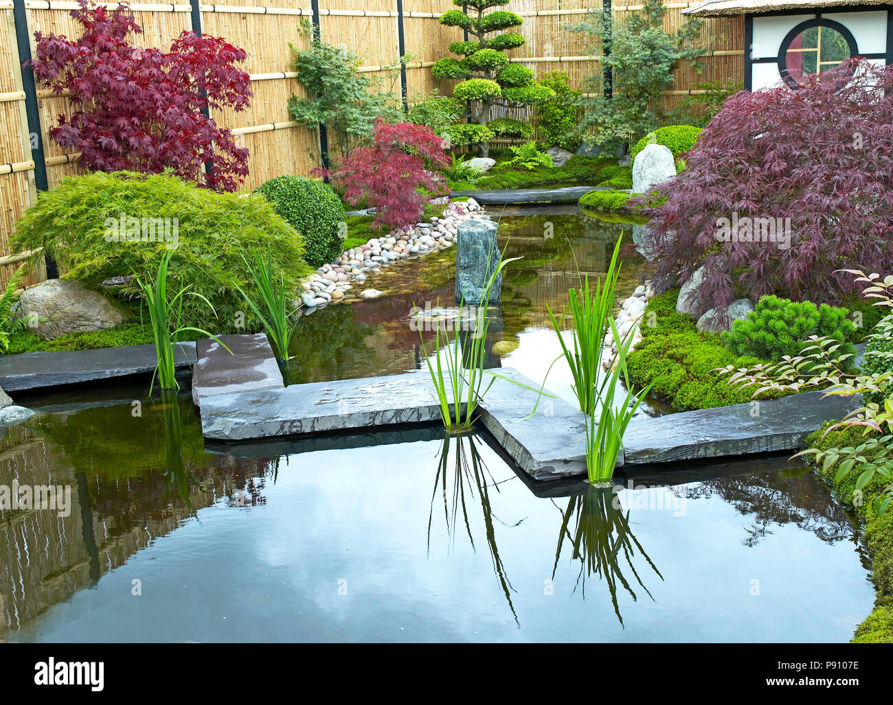 Traditional Japanese Water Garden With Plants, Shrubs, Rocks, Tea House And  Stone Bridge