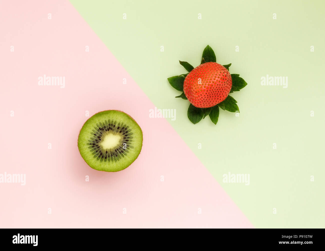 One Kiwi half and one Strawberry on duo color background - Stock Image