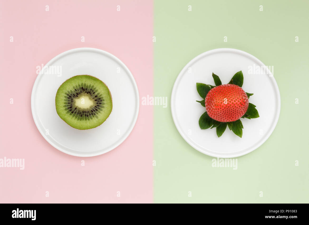 One Kiwi and one Strawberry on duo color background - Stock Image