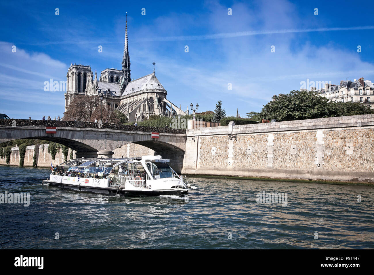 A tourist boat on the River Seine cruises by Notre Dame under the Pont Archeveche bridge.  Paris, France. - Stock Image