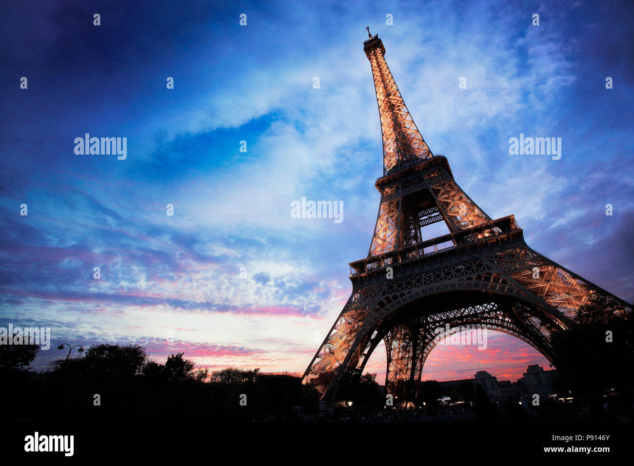 The Eiffel Tower lights up at dusk.  Paris, France. - Stock Image