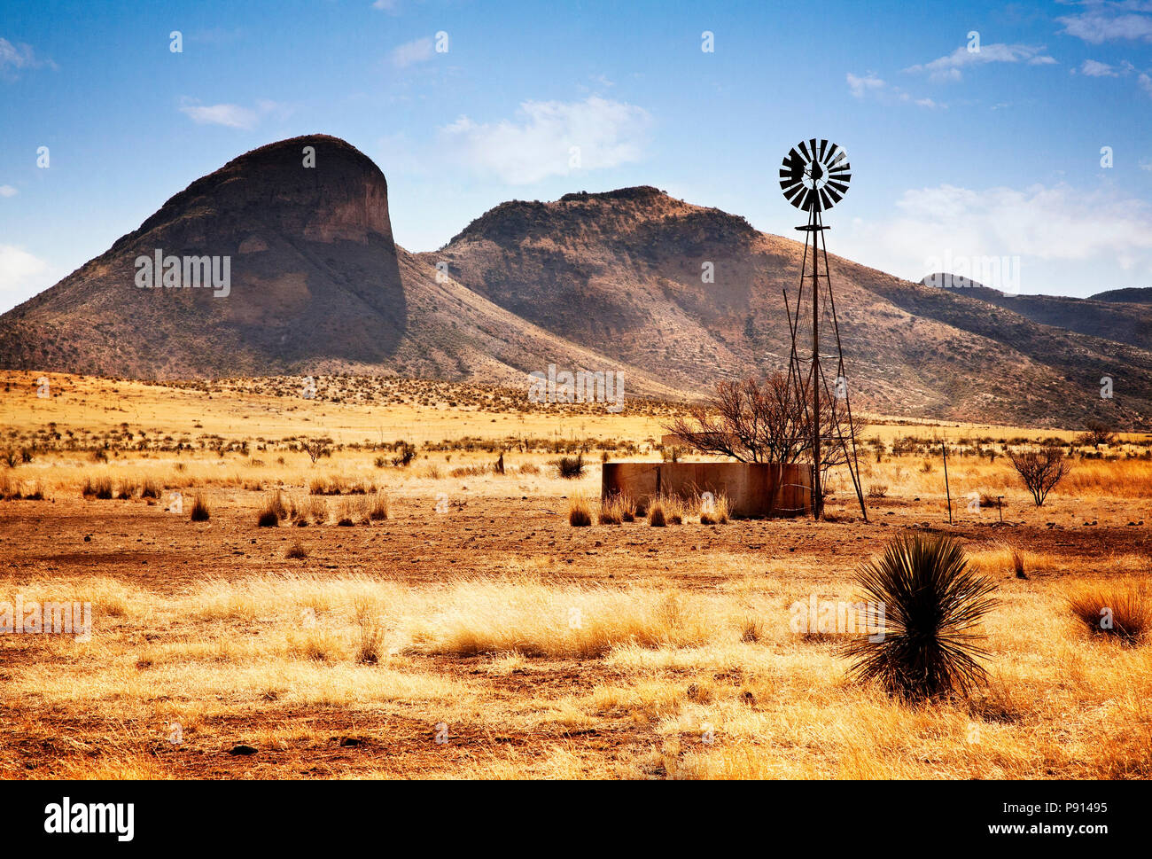 A wind wheel pumps water for livestock in dry pastureland in the southeast desert of Arizona. - Stock Image