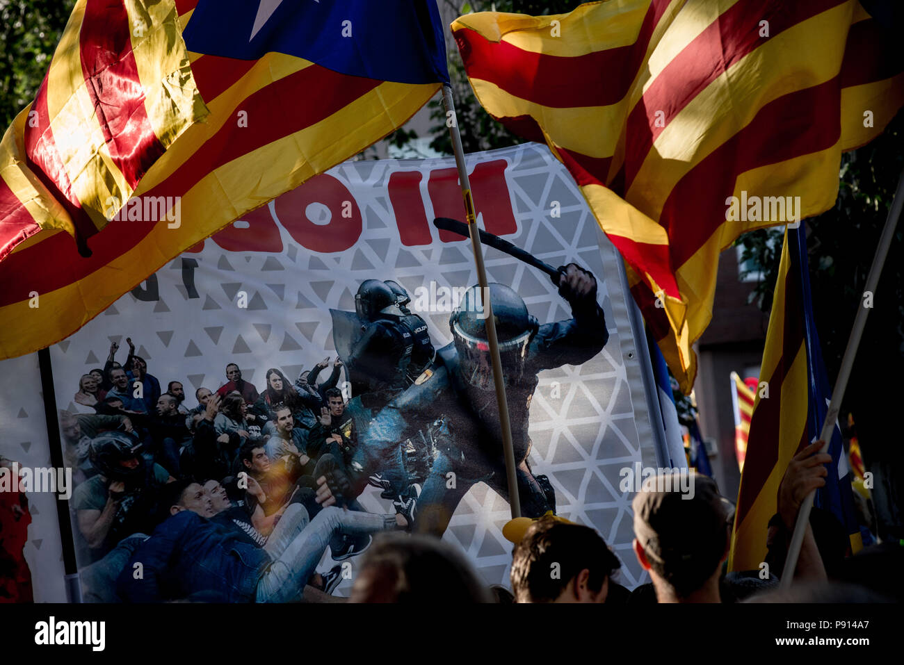 A banner showing the police brutality of the first October   referendum is seen among estelades or pro-independence flags in Barcelona. Tens of thousa - Stock Image