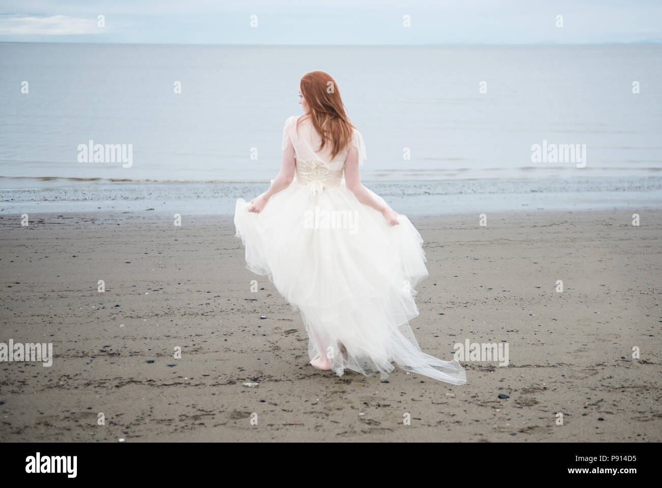 4c8cae5b3febd View from behind of beautiful redhead young woman on the beach, wearing a  flowing, white dress.