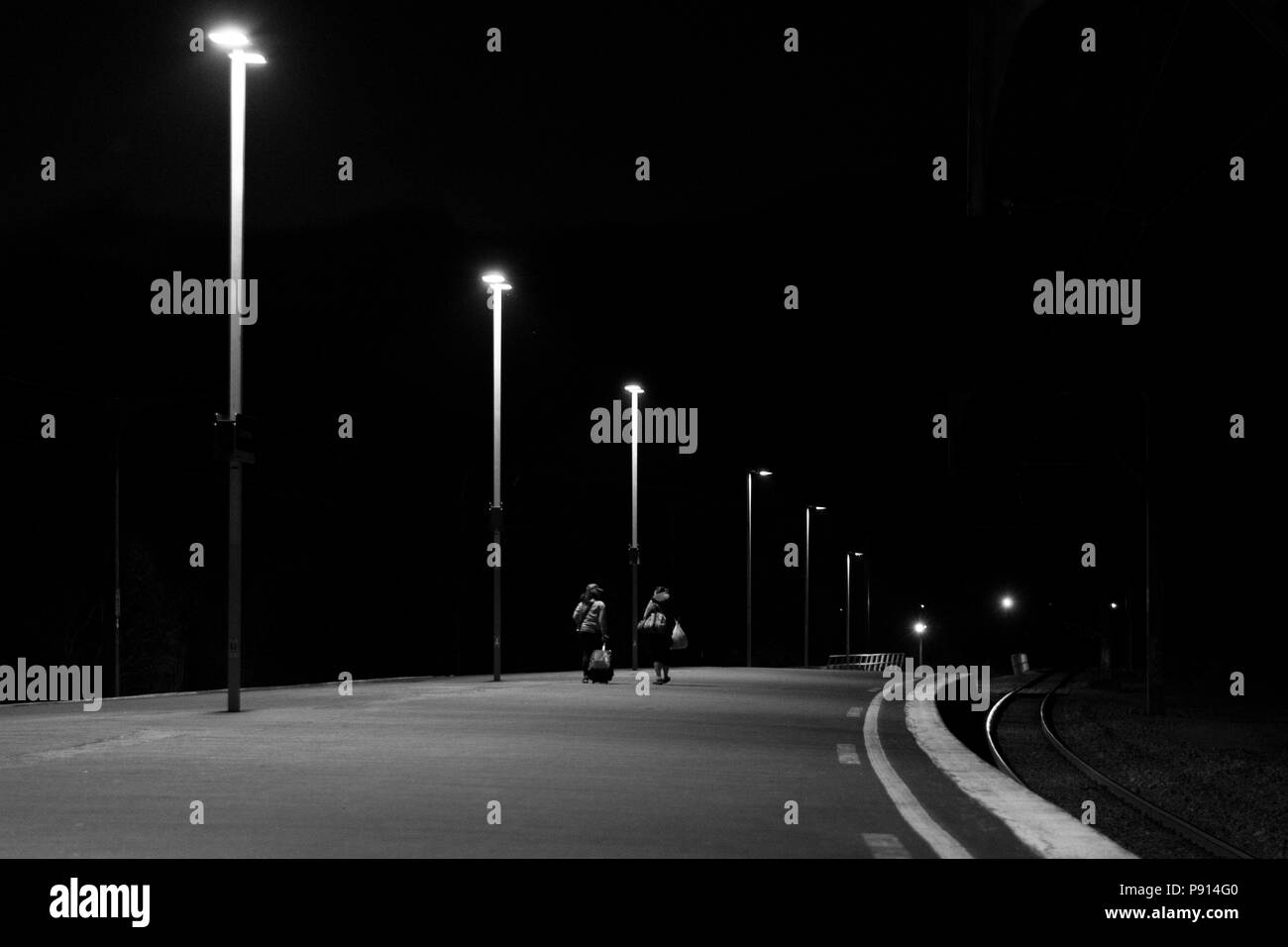 Two people walking down a train station at night carrying luggage with flood lights leading into the distance - Stock Image