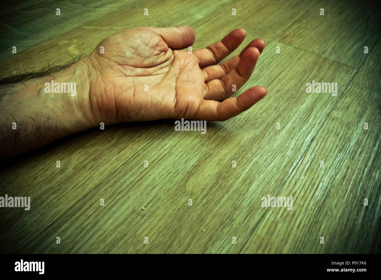 male hand and arm lying on the floor, dead - Stock Image