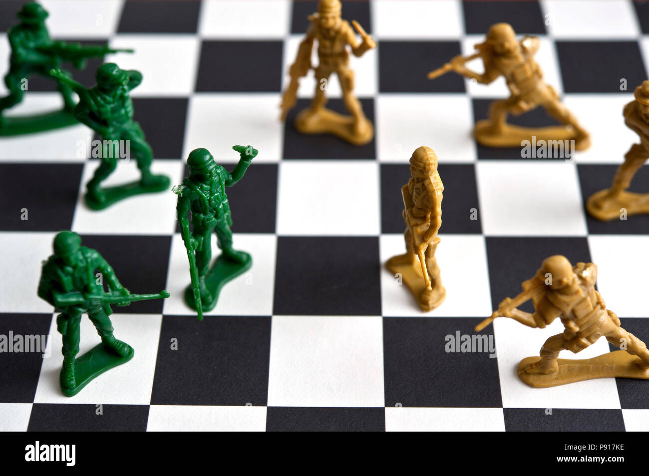 two armies of plastic toy soldiers facing each other on a checkerboard - Stock Image