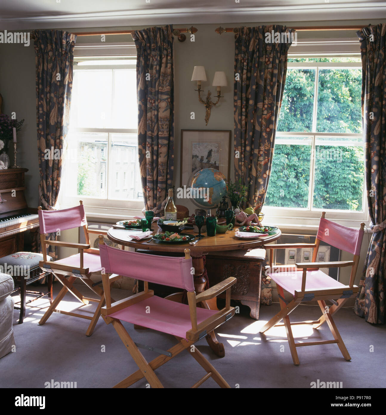 Pink Director S Chairs And Circular Pine Table In Front Of Windows With Floral Curtains In Apartment Dining Room Stock Photo Alamy