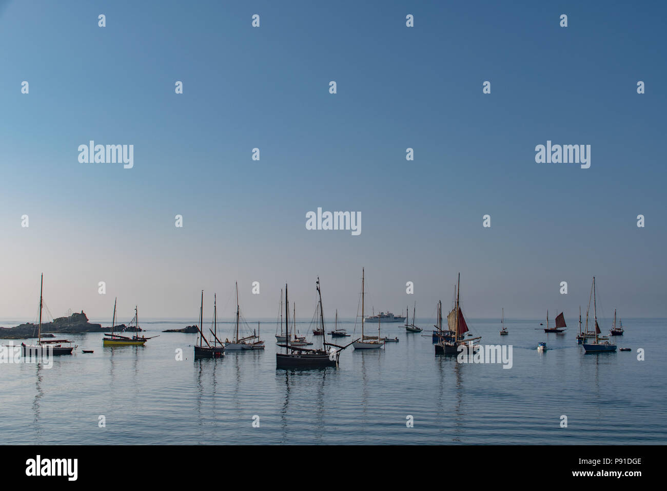 """Mousehole, Cornwall, UK. 14th July 2018. UK Weather. The sea was calm and it was hot early in the morning for these visting yachts to the Mousehole Sea Salts and Sail festival which is on over the weekend. Some even took to walking the """"plank"""" and jumping into the sea for an early morning dip. Credit: Simon Maycock/Alamy Live News Stock Photo"""
