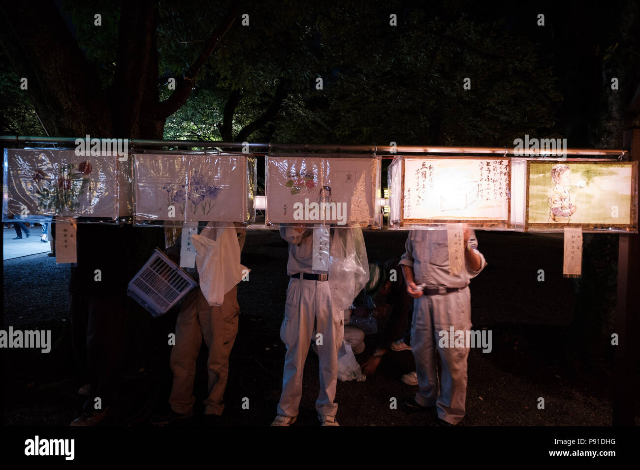Tokyo, Japan, 13 July 2018. Yasukuni shrine staff changes light bulb of lit paper lanterns during the Mitama Matsuri summer festival at Yasukuni Shrine on July 13, 2018 in Tokyo, Japan. The four-day traditional festival takes place during Tokyo's Bon period in July attracting about 300,000 visitors, according to the shrine. July 13, 2018 Credit: Nicolas Datiche/AFLO/Alamy Live News - Stock Image