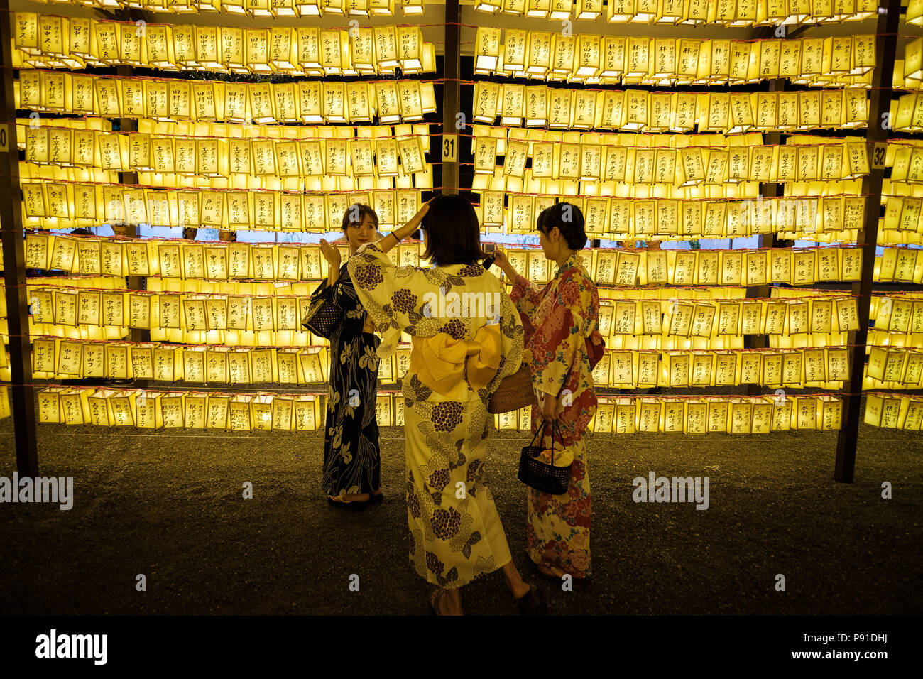 Tokyo, Japan, 13 July 2018. Young ladies wearing yukata (traditional kimono for summer) enjoy paper lanterns during the Mitama Matsuri summer festival at Yasukuni Shrine on July 13, 2018 in Tokyo, Japan. The four-day traditional festival takes place during Tokyo's Bon period in July attracting about 300,000 visitors, according to the shrine. July 13, 2018 Credit: Nicolas Datiche/AFLO/Alamy Live News - Stock Image