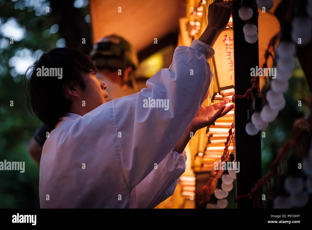Tokyo, Japan, 13 July 2018. Yasukuni shrine staff hangs a lit paper lanterns during the Mitama Matsuri summer festival at Yasukuni Shrine on July 13, 2018 in Tokyo, Japan. The four-day traditional festival takes place during Tokyo's Bon period in July attracting about 300,000 visitors, according to the shrine. July 13, 2018 Credit: Nicolas Datiche/AFLO/Alamy Live News - Stock Image
