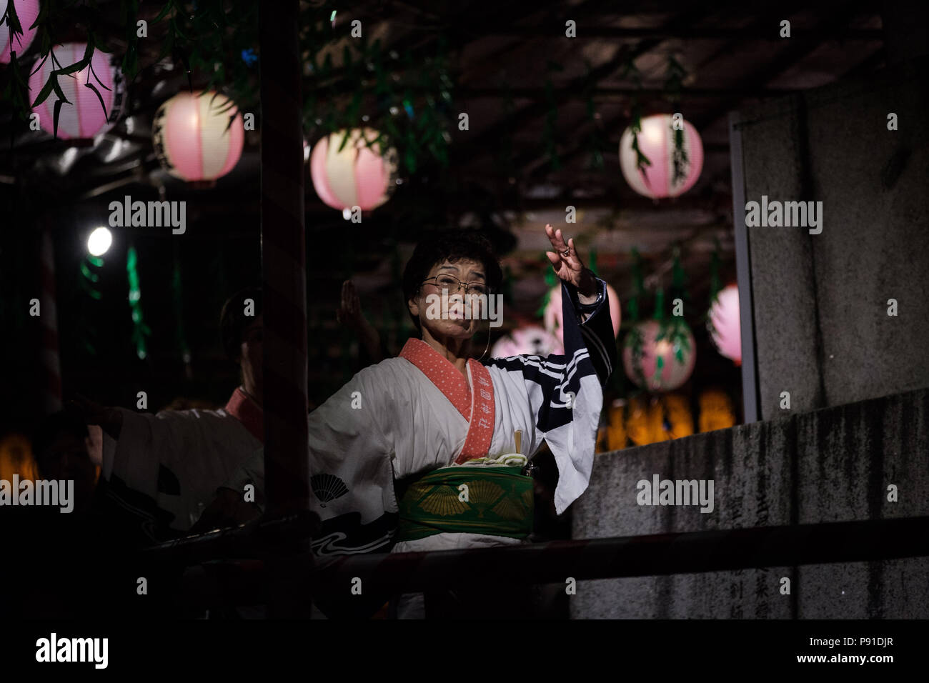 Tokyo, Japan, 13 July 2018. People dance on traditional festival music with lit paper lanterns on background during the Mitama Matsuri summer festival at Yasukuni Shrine on July 13, 2018 in Tokyo, Japan. The four-day traditional festival takes place during Tokyo's Bon period in July attracting about 300,000 visitors, according to the shrine. July 13, 2018 Credit: Nicolas Datiche/AFLO/Alamy Live News - Stock Image