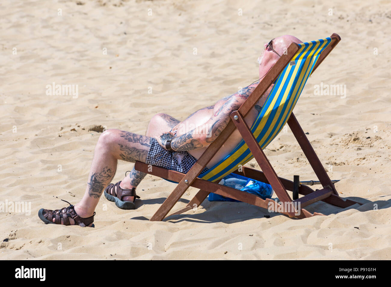 Bournemouth, Dorset, UK. 14th July 2018. UK weather: The heatwave continues with another hot sunny day, as sunseekers make the most of the glorious weather and head to the seaside at Bournemouth beaches. Man sunbathing in deckchair. Credit: Carolyn Jenkins/Alamy Live News - Stock Image