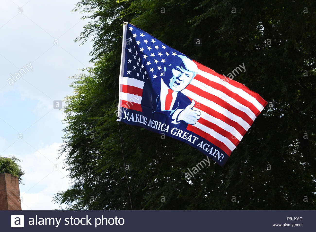 London, United Kingdom. 14th July, 2018. A Make America Great Again flag flies as hundreds of Trump supporters gather outside the US embassy in London, UK on July 14, 2018 for a Welcoming Trump to London rally in the British capital. (c) copyright Credit: CrowdSpark/Alamy Live News - Stock Image