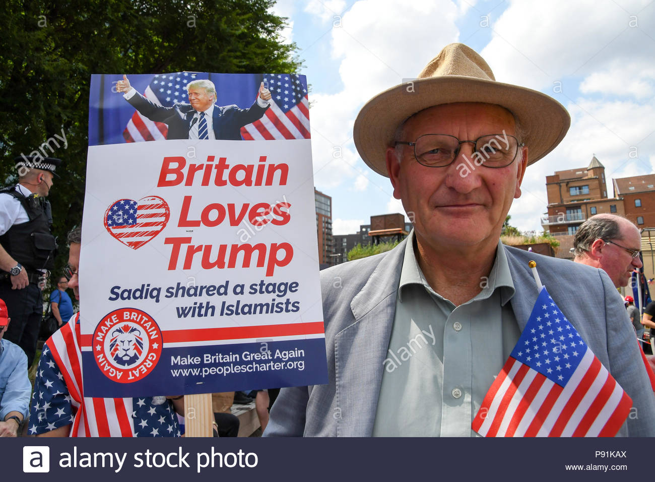 London, United Kingdom. 14th July, 2018. A protester holds a sign reading 'Britain loves Trump, Sadiq shares a stage with Islamists' as hundreds of Trump supporters gather outside the US embassy in London, UK on July 14, 2018 for a Welcoming Trump to London rally in the British capital. (c) copyright Credit: CrowdSpark/Alamy Live News - Stock Image