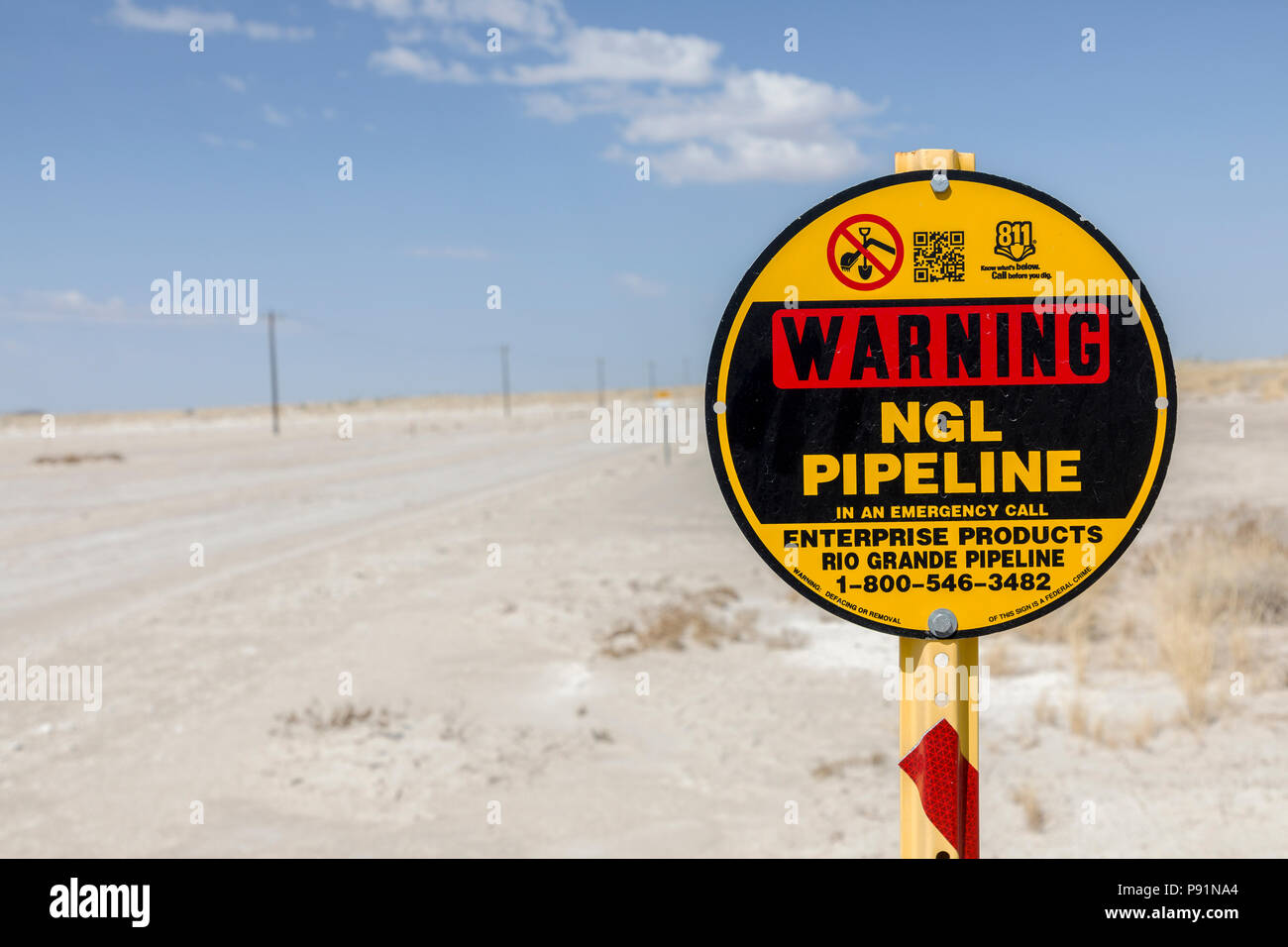 Warning sign for buried pipeline in desert, New Mexico, USA - Stock Image