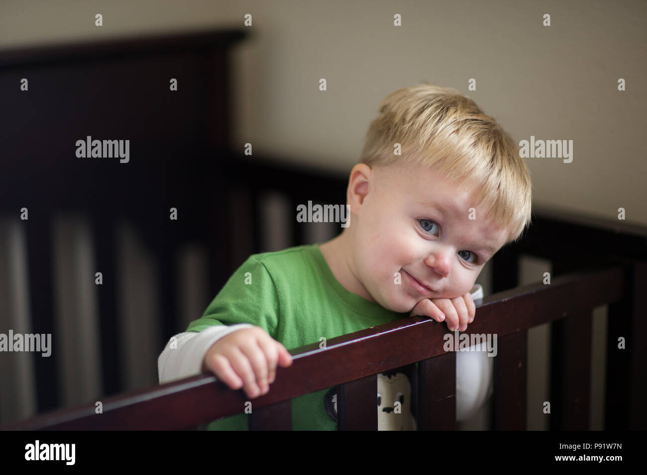 Toddler is in his crib smiling while wanting to get out. - Stock Image