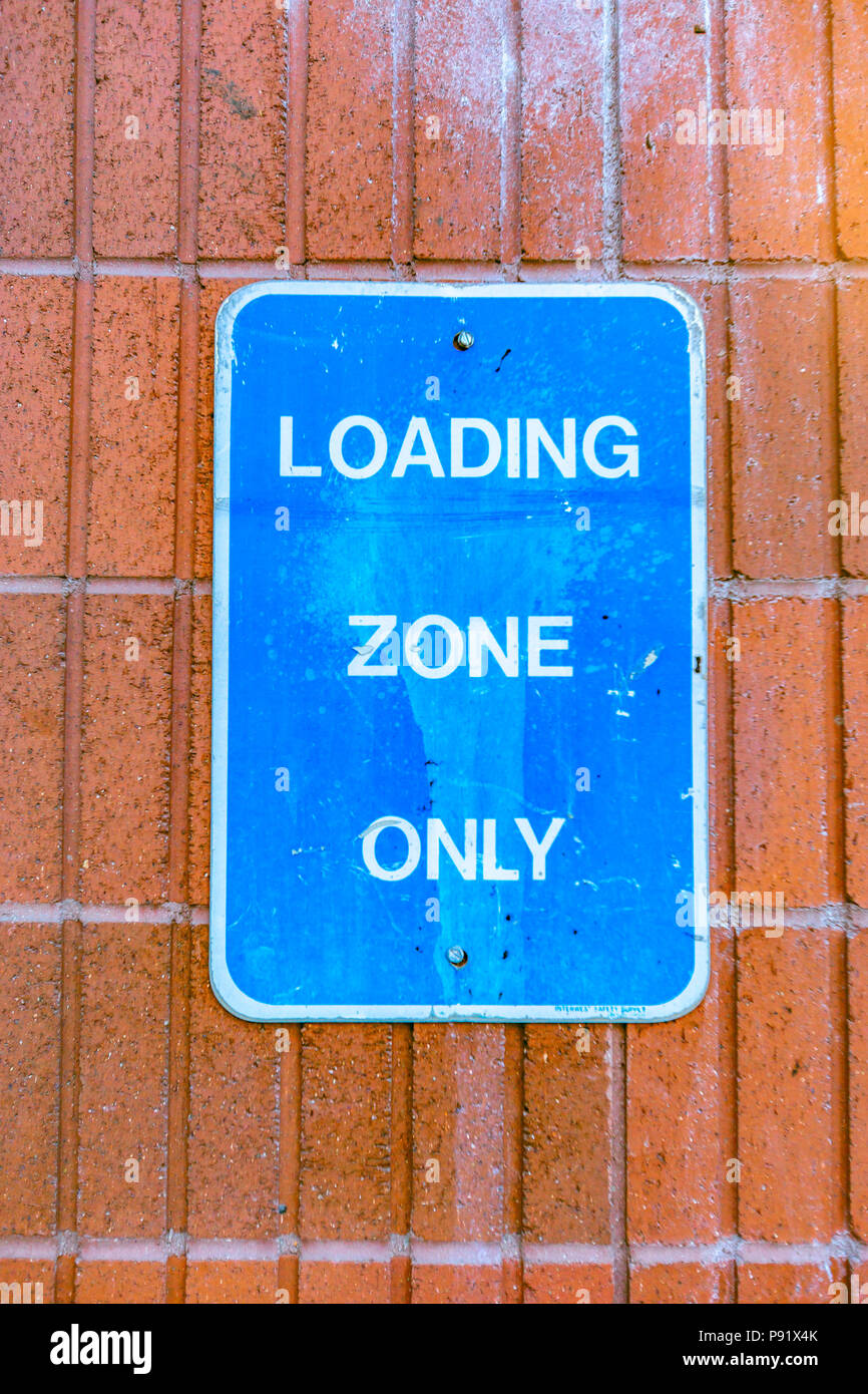 Loading zone only blue sign against brick - Stock Image