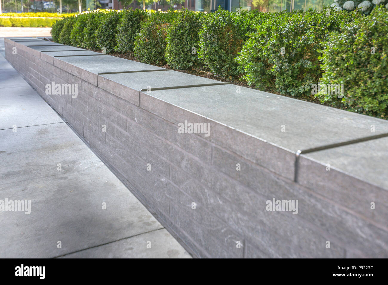 Metal gaurds on the edge of concrete planter - Stock Image