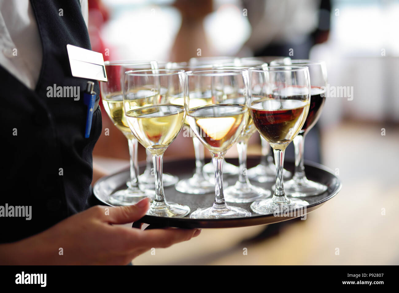 Waitress holding a dish of champagne and wine glasses at festive ...