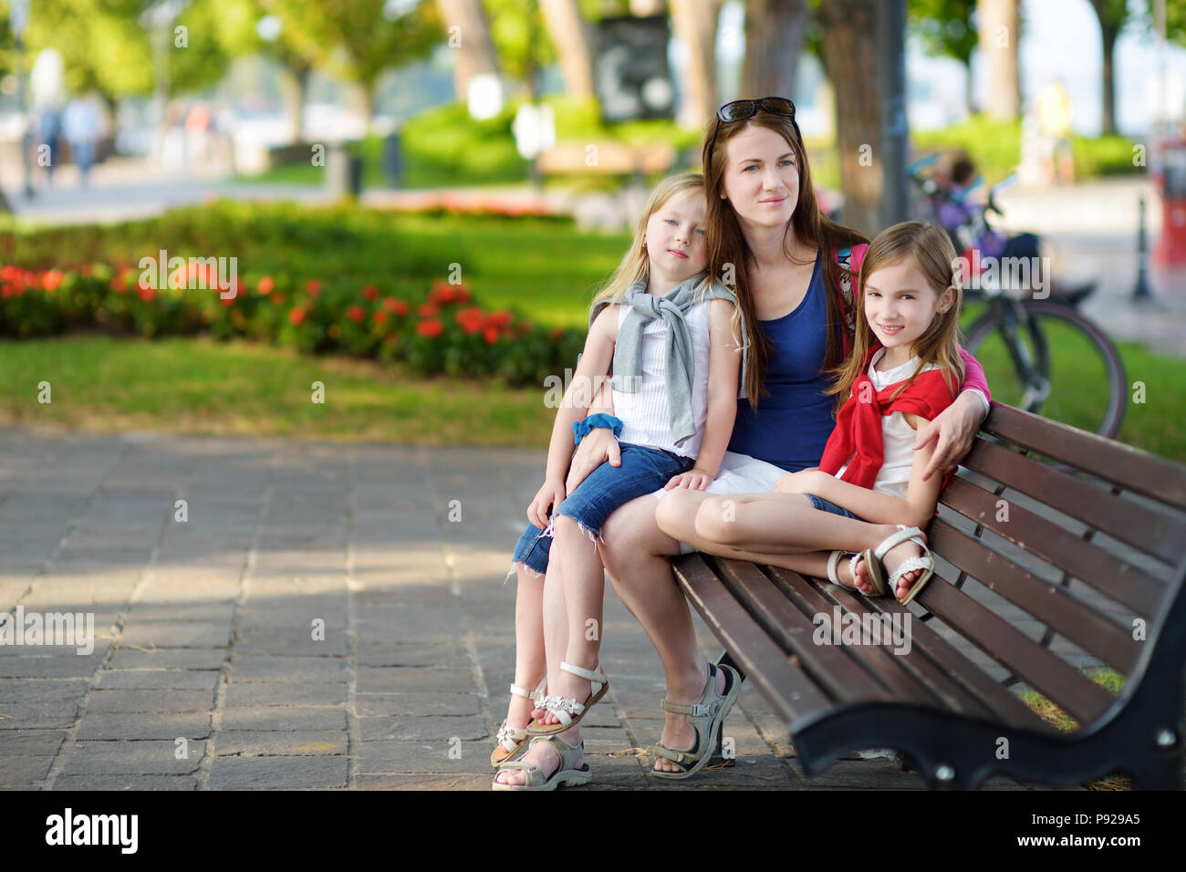 Young mother and two cute little sisters sitting on a bench hugging on warm and sunny summer day in italian town - Stock Image