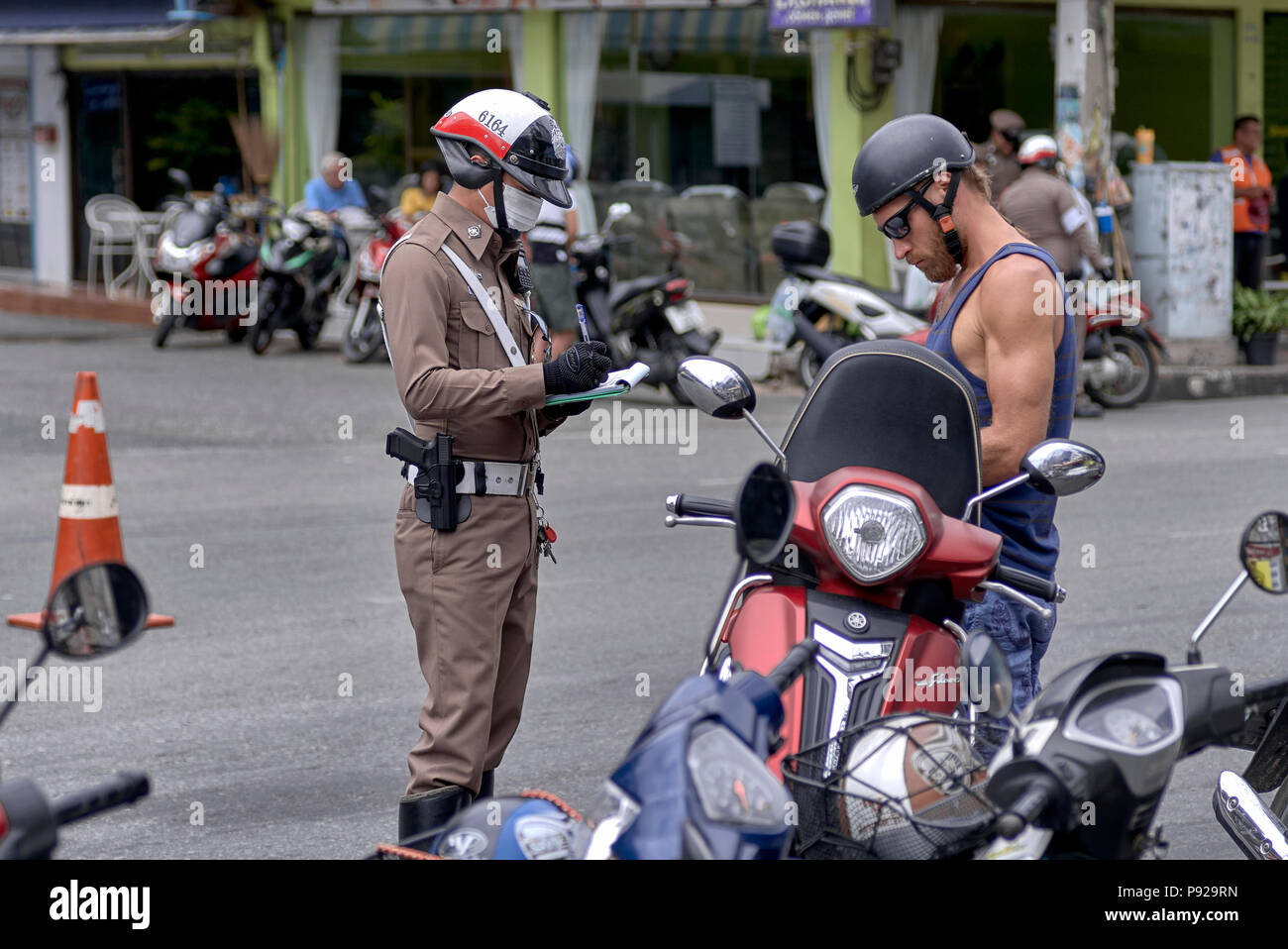 Thailand traffic police with officer issuing a violation ticket to offending motorcycle rider Stock Photo